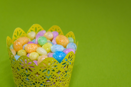 jelly beans: Jelly beans in a yellow metal basket on a green background