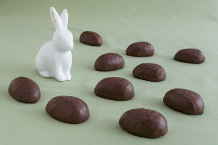 White ceramic Easter bunny in a field of chocolate covered marshmallow eggs on a green background