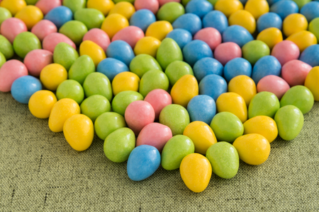 Yellow, pink, blue, and green Easter candy on a green background