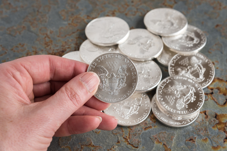 legal tender: Hand holding an American silver dollar above a pile of silver dollars on a slate background Stock Photo