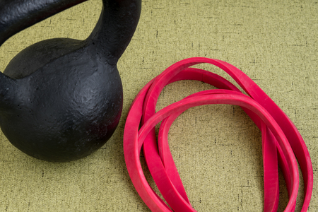 Black kettle bell and red resistance band on a light green background