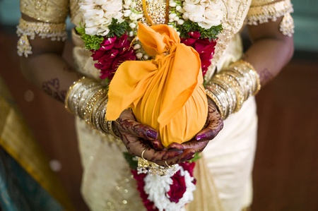 offering: ndian bride with henna decoration on her hands, holding one of the wedding presents Stock Photo