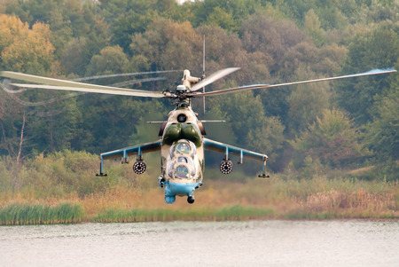 vortices: Combat helicopter Mi-24 flying over the water surface.
