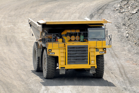 dump truck: Yellow dump truck  driving on a road in a stone quarry