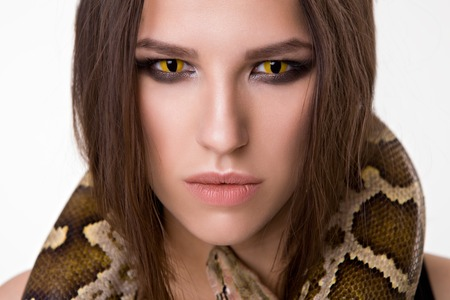 snake eyes: Serious women with smoky eyes and snake around her neck look at the camera. Isolated on white Stock Photo