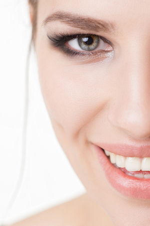 Close-up femme visage avec le maquillage des yeux charbonneux sourire