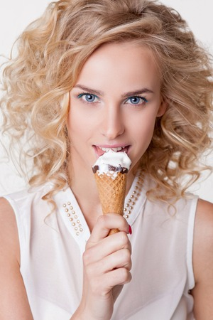 Close-up women with perfect skin, trendy make-up and curly hair eating ice-cream isolated on white