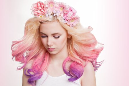 Youth women with curly colored hair and flowers. white and pink background. Beauty