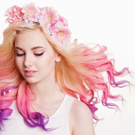 Jeugd vrouwen met krullend gekleurd haar en bloemen. witte en roze achtergrond. Schoonheid. vliegende Haren Stockfoto