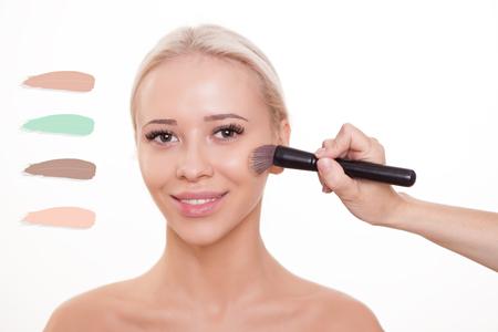 La cara modelo de mujer hermosa con base sobre la piel de maquillaje cosméticos. Aplicar la base tonal líquido en la cara