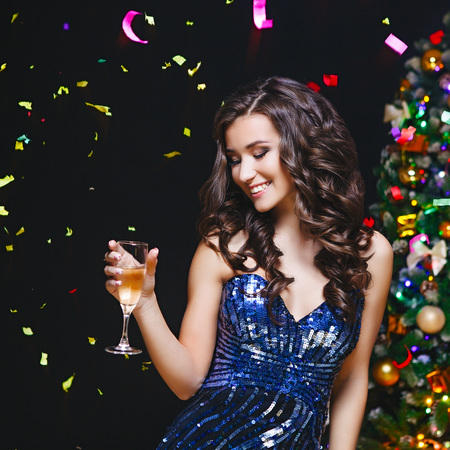 Celebrating Woman. Holiday People. Beautiful Girl with Makeup Holding Glass of Champagne. Dark background 스톡 콘텐츠