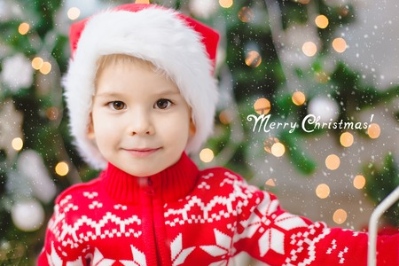 good wishes: Little boy in santa claus hat looks at the camera and smile. Bokeh background. Copy-space. Text contains good wishes. Christmas. Holiday