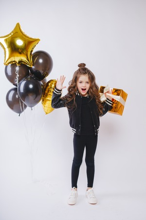 Little modern hipster girl in fashion clothes stand near balloons and hold gold present. Pose face. Birthday. Studio