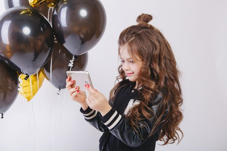 Little modern hipster girl in fashion clothes and baloons, Selfie. Take photo on telephone. Studio