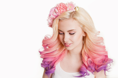 Youth women with colored hair smiling. Flowers in her hair. Studio, isolated, white background. Concept spring, summer. look down. Gradient Stock Photo