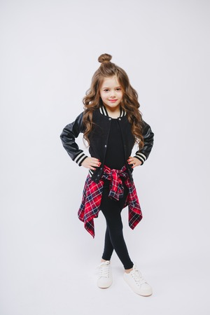 Portrait of little hipster girl in bomber jacket. Posing. Curly modern hairstyle. Smiling. Studio