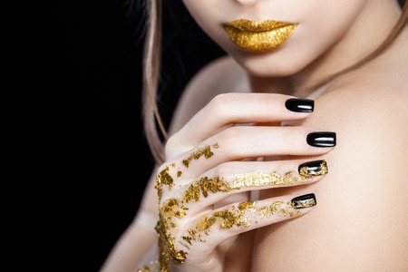Beautiful Fashion woman model face portrait with gold lipstick and black nails. Glamour girl with bright makeup. Beauty female. Perfect skin and make up. Nail polish. Isolated on black Stock Photo