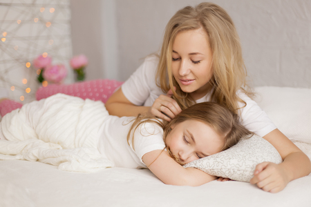 mother put her daughter to sleep. White interior Stock Photo - 75425353