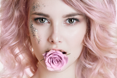 marshmellow: Colored hair. Beauty women portrait. half face of young curly woman with pink hair, perfect art make-up with glitter. Rose in her mouth. Studio