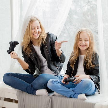 Juegos familiares Madre e hija juegan juntos en conlsole Foto de archivo - 76973528