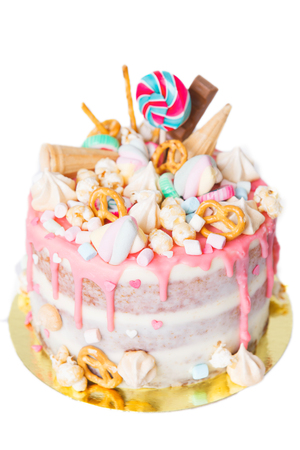 birthday cake with decorated with candies, lollipop, marshmallows. Pink pastel color. Balloons on background