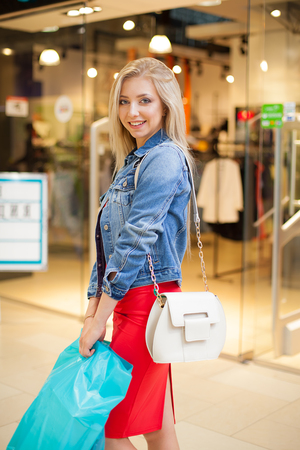 Concept Shopping. Portrait of beauty blonde smiling woman in casual holding shopping bags near shop in the shopping center. Indoor Stock Photo
