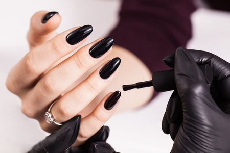 Beauty salon. Master making black manicure in black gloves. White background Foto de archivo