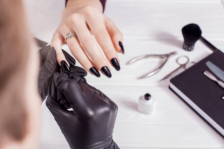 Beauty salon. Master making black manicure in black gloves. White background. Salon. Nail scissors Foto de archivo