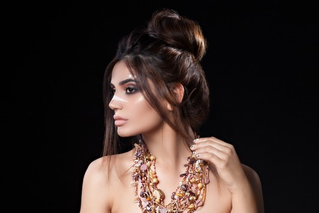 Portrait of beautiful woman with sensitive sexy view, gold nails design and jewelery with natural stones. Ethnics. Studio Standard-Bild