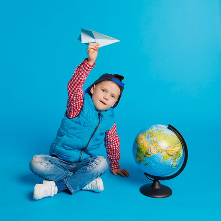 portrait of little funny boy with cap and toy paper plane. Showing place on the globe, map. Concept travel, education. On the blue background