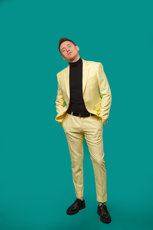 Attractive young man in suit dancing, having fun on mint background. Stylish outlook, successful businessman, happy, expressing true positive emotions, funny. Place for text. Studio Stock Photo