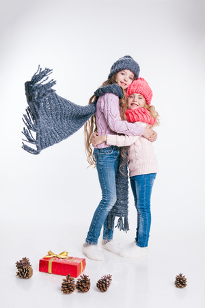 Christmas. New Year. Two little sisters holding present in winter clothes. Pink and grey hats and scarfs. Happy Family. Winter. Isolated