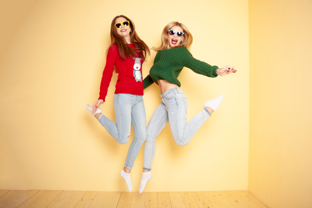 Two funny beautiful hipster girls in sweaters and sunglasses. Concept winter and fashion.Jumping. Flying hairs