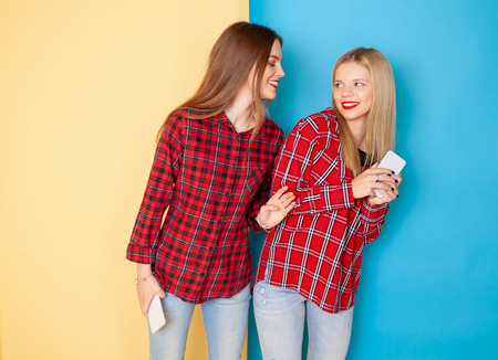 Portrait of young happy women friends standing over yellow and blue wall. Chat, make fun and selfie.