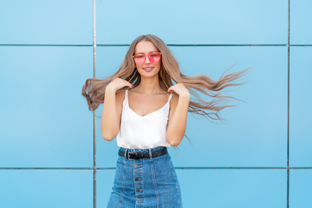 Portrait of beauty fashion smiling woman with flying hairstyle, in pink neon sunglasses on blue background. Casual. Copyspace