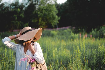 Beautiful woman in a big hat enjoing the sun on a field with flowers. Summer lifestyle. Outdoor