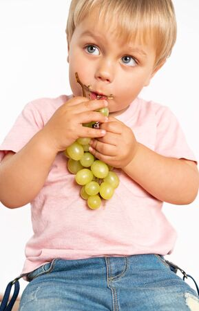 Baby boy eating grapes and smiling in the studio isolated on white background. Concept healthy fresh food Foto de archivo - 130774195