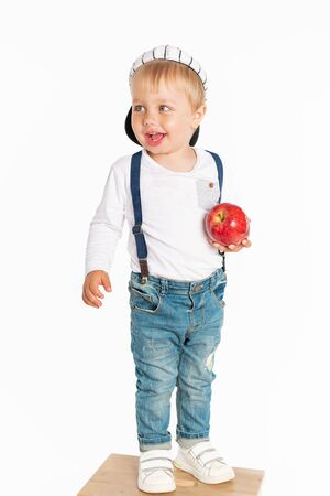 Baby boy eating apple and smiling in the studio isolated on white background. Concept healthy fresh food Foto de archivo - 130774303