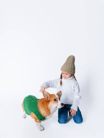 Portrait of young little girl with her pet puppy of corgi. Concept christmas, new year and birthday. Isolated on white Foto de archivo - 130774523