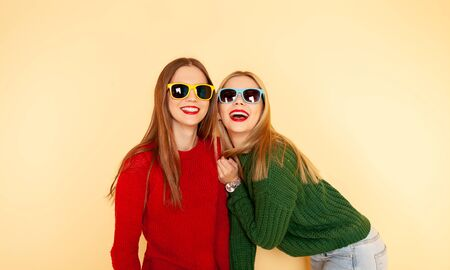 Two funny beautiful hipster girls in sweaters and sunglasses. Concept winter and fashion. Isolated on yellow Foto de archivo - 131875467