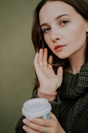Beautiful woman with freckles on her face in knitted sweater, holding cup of coffee on the street. Green background. Autumn, Winter Foto de archivo - 133206271