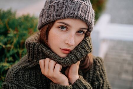 Beautiful woman with freckles on her face in knitted sweater on the street. Green background. Autumn, Winter 스톡 콘텐츠