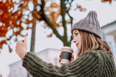 Beautiful woman with freckles on her face in knitted sweater and hat, holding cup of coffee on the street and making selfie by smartphone. city lifestyle. Autumn, Winter Foto de archivo - 133206279