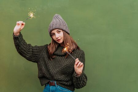 Beautiful woman with freckles on her face in knitted sweater and hat on the street and holding bengal light. city lifestyle. Autumn, Winter 스톡 콘텐츠