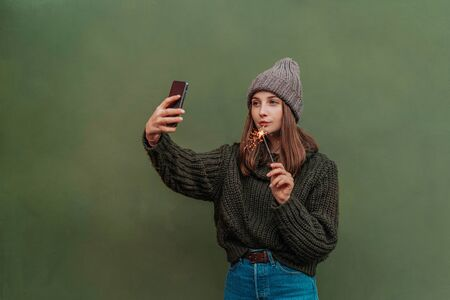 Beautiful woman with freckles on her face in knitted sweater and hat, holding bengal light on the street and making selfie by smartphone. city lifestyle. Autumn, Winter Foto de archivo - 133206285