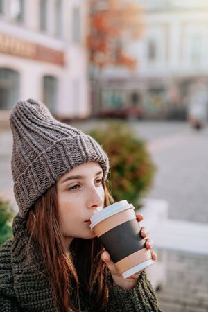 Beautiful woman with freckles on her face in knitted sweater and hat, holding cup of coffee on the street. city lifestyle. Autumn, Winter Foto de archivo - 133206288