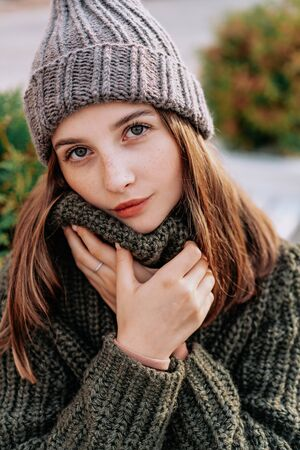 Beautiful woman with freckles on her face in knitted sweater on the street. Green background. Autumn, Winter 스톡 콘텐츠 - 133206297