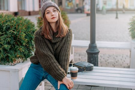 Beautiful woman with freckles on her face in knitted sweater and hat, holding cup of coffee on the street. city lifestyle. Autumn, Winter Foto de archivo - 133206313