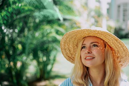Portrait of beautiful of traveler woman with hat smiling behind palm trees. Sunlight. Concept travel, vacation, dream Foto de archivo - 133206461