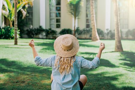 Portrait of beautiful of traveler woman with hat doing yoga behind palm trees. Sunlight. Concept travel, vacation, dream,sport Foto de archivo - 132265323